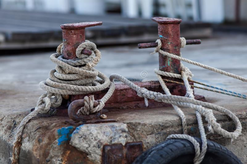 Two-headed mooring bitt wrapped with rope stock photo