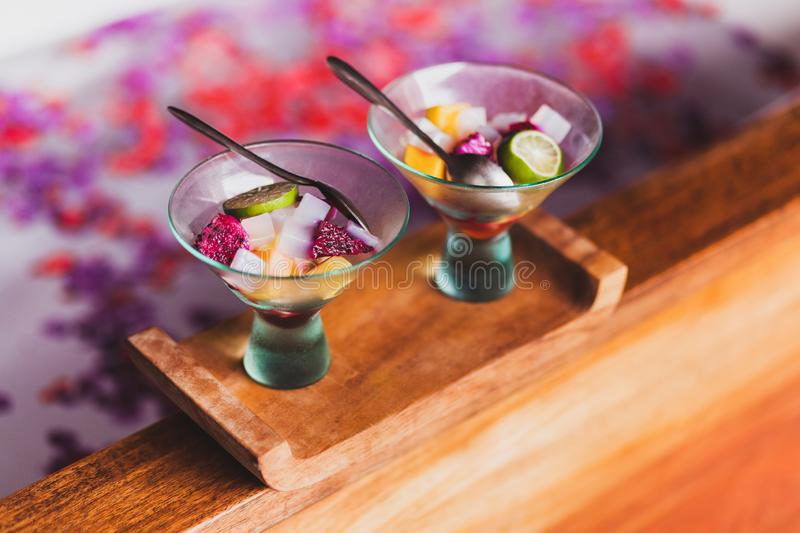 Two healthy fruit salad on wooden edge of bath spa. Two organic and health fruit salad on wooden edge of bath in spa. Healthy eating after relaxation treatment stock image