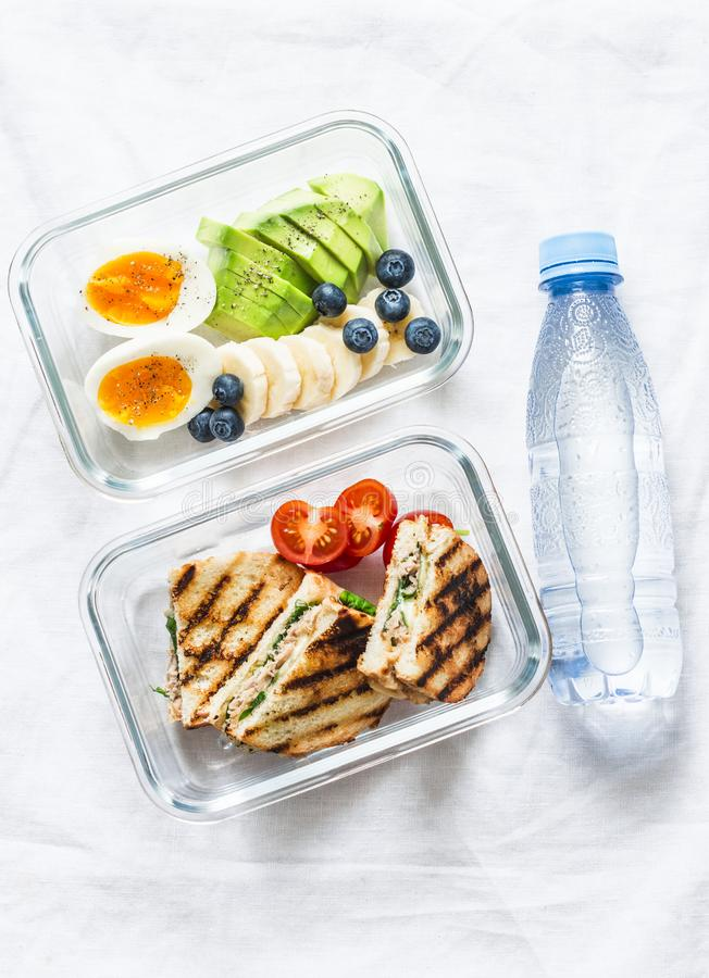 Two healthy office lunch box with sweet, savoury food. Boiled egg, avocado, tuna spinach cheese sandwiches, fruit and bottle stock photo