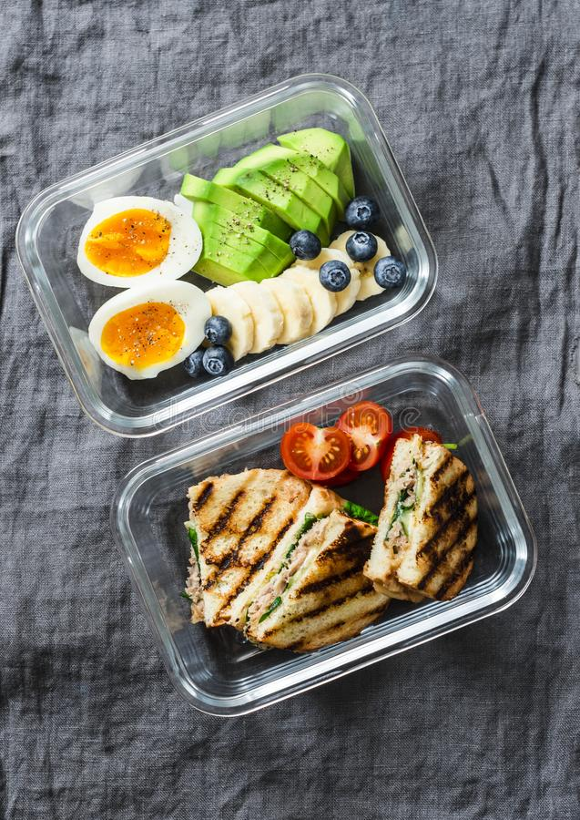 Two healthy office lunch box with sweet and savoury food. Boiled egg, avocado, tuna spinach cheese sandwiches and fruit royalty free stock image
