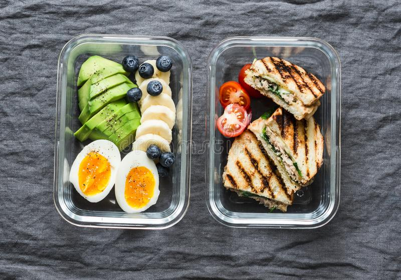 Two healthy office lunch box with sweet and savoury food. Boiled egg, avocado, tuna spinach cheese sandwiches, fruit on grey royalty free stock images