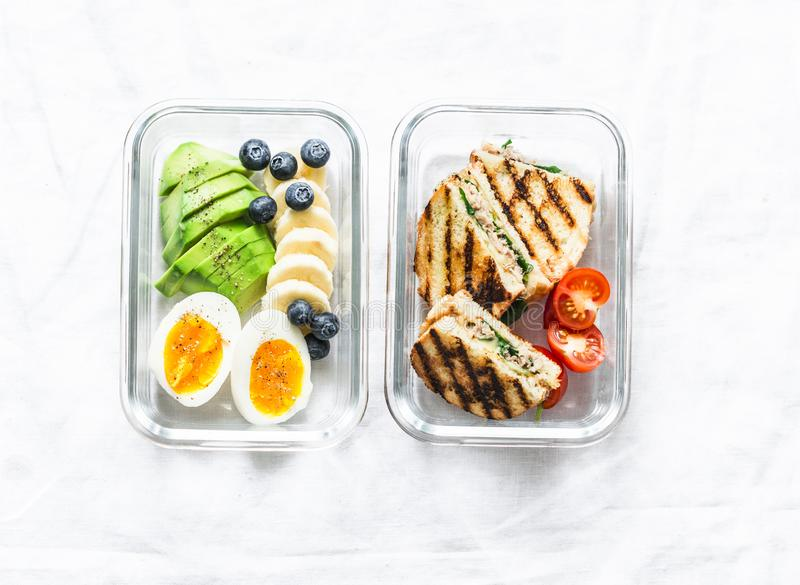 Two healthy office lunch box with sweet, savoury food. Boiled egg, avocado, tuna spinach cheese sandwiches, fruit on a light royalty free stock photography