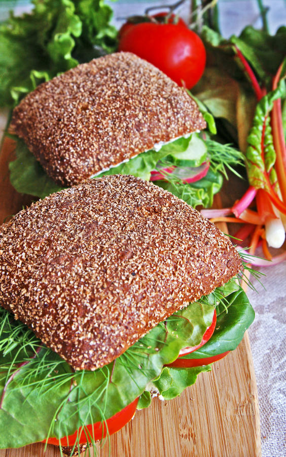 Two healthy rye bread sandwiches on a wooden board