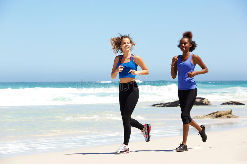 Two healthy young female runners. Full body portrait of two healthy young female runners at the beach stock photos