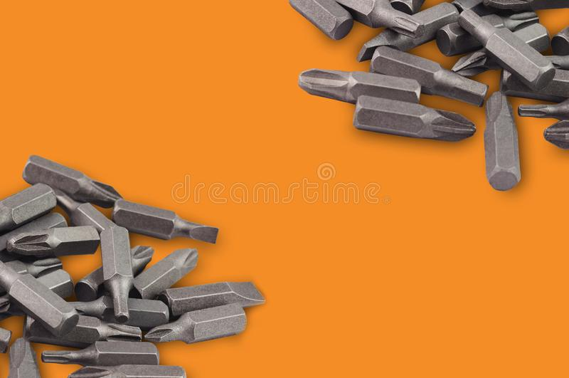 Two heaps of different interchangeable heads or bits for manual screwdriver for woodworking and metalworking on orange background stock images