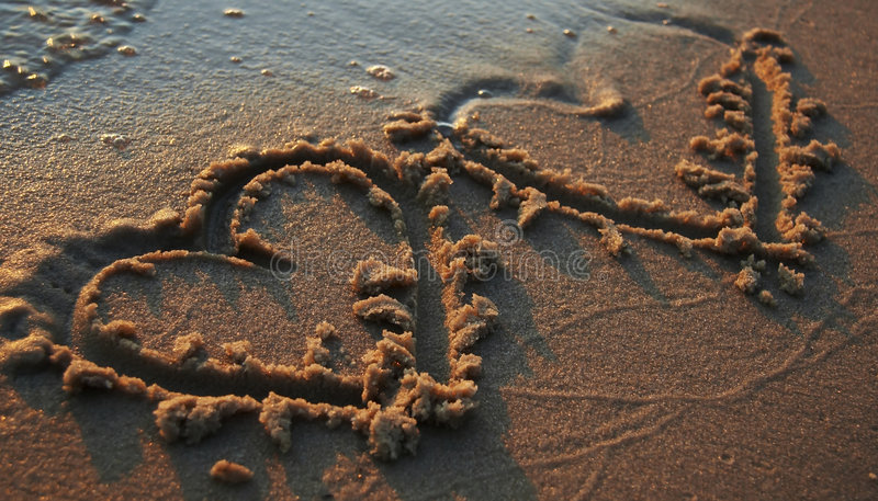 Two heards on sand. Valentine theme-Two hearts on sand stock photography