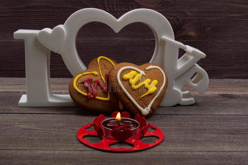 Two heart shaped cookies, a red candle and the word love on a wooden table. On Valentine's Day royalty free stock images