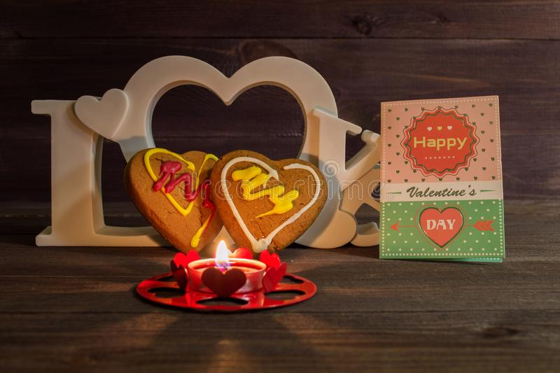Two heart shaped cookies, a red candle and the word love on a wooden table. On Valentine's Day stock photo