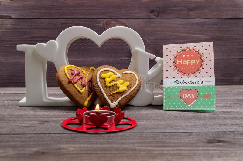 Two heart shaped cookies, a red candle and the word love on a wooden table. On Valentine's Day stock images