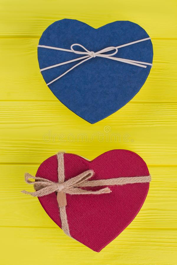 Two heart-shaped gift boxes vertical disposition. Top view. Yellow wooden background stock photo