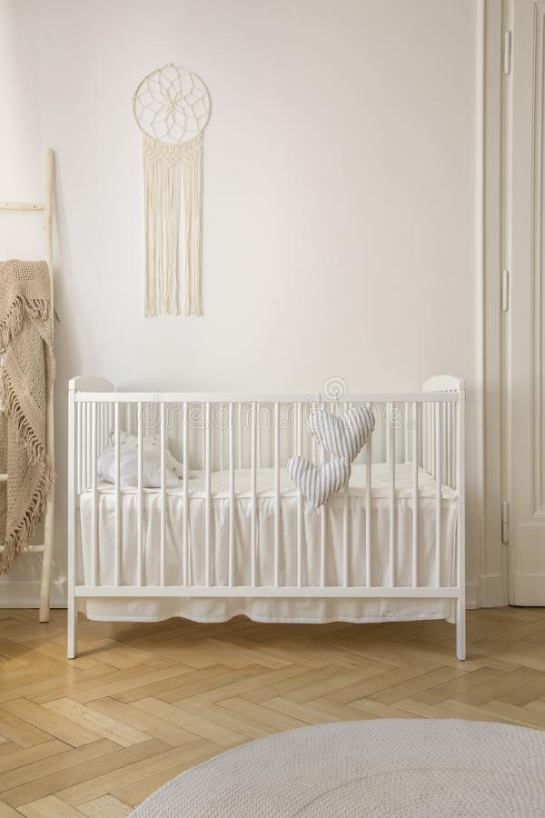 Two heart shaped pillows placed on baby crib standing in white room interior with macrame on wall and herringbone parquet stock image