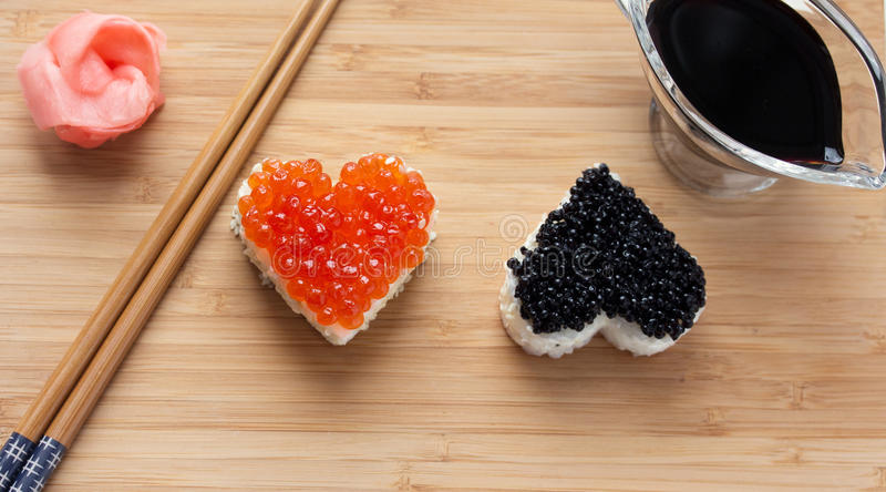 Two heart shaped sushi with salmon roe and beluga royalty free stock photos