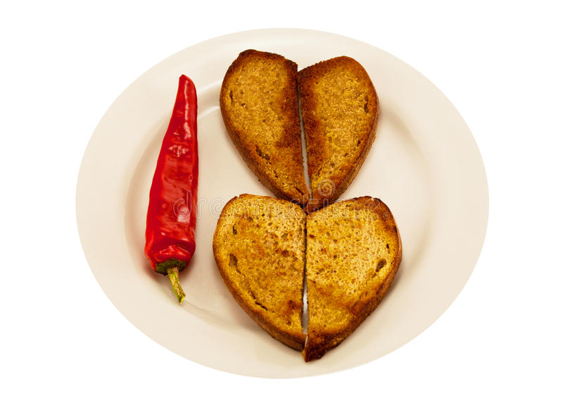 Two heart-shaped toast and spicy red pepper stock photography