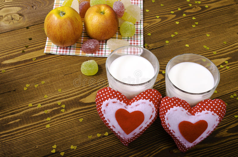 Two hearts, apples on a napkin and two glasses of milk. stock photos