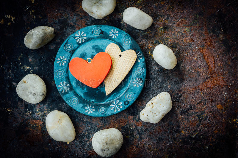 Two hearts on blue plate over rustic background stock photography