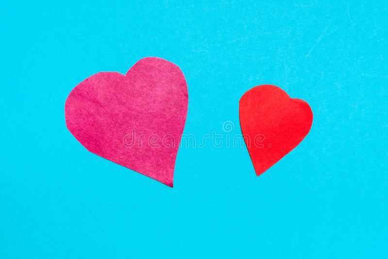 two hearts cut from red papers on blue paper stock photo