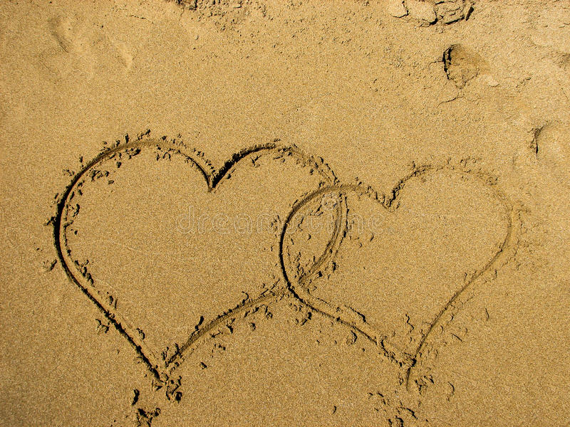 Two hearts drawn on sand of a beach. Valentines day on the beach. Top view, Horizontal composition royalty free stock images