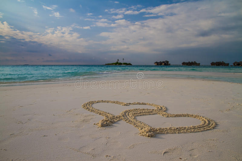 Two hearts drawn in the sand at the tropical beach royalty free stock photo
