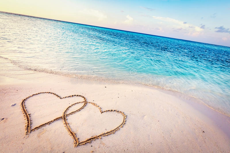 Two hearts drawn on sand of a tropical beach at sunset. stock photos