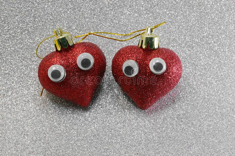 Two hearts with eyes on silver background ideal as a conceptual. Two red big hearts with eyes on the bright silver color background ideal as a conceptual idea of royalty free stock photos