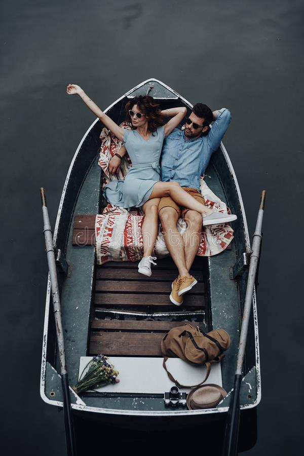 Two hearts full of love. Top view of beautiful young couple embracing while lying in the boat royalty free stock photography