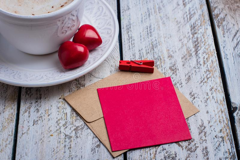Two hearts, gift card and cup of coffee on white wooden table background. Morning greeting. Valentine`s day concept, top view, royalty free stock photos