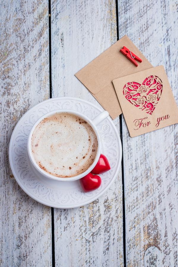 Two hearts, gift card and cup of coffee on white wooden table background. Morning greeting. Valentine`s day concept, top view, stock image