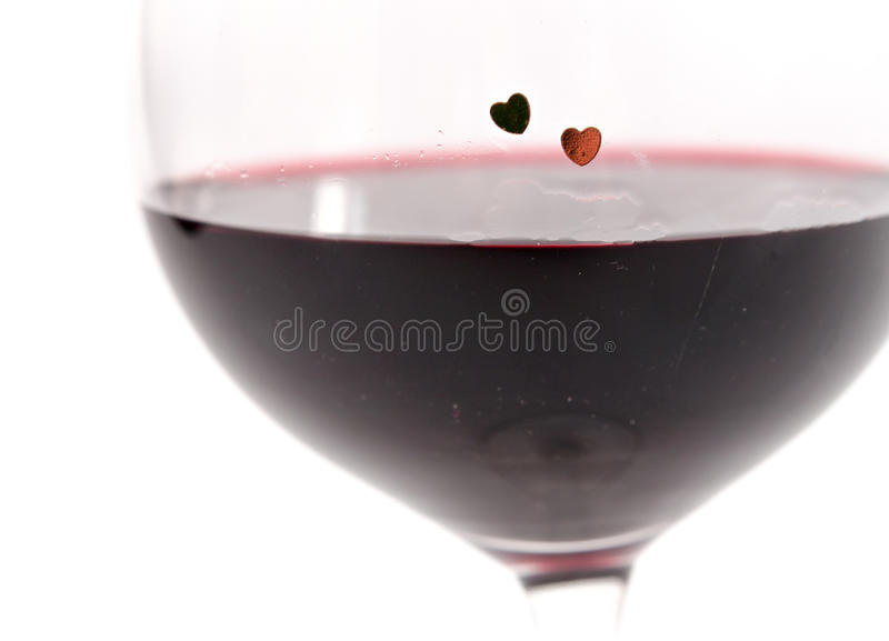 Two hearts on a glass with red wine on white background stock image