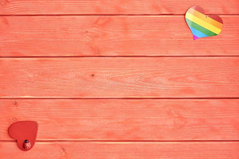 Two hearts lie on a wooden background color of living coral. One heart with a rainbow of LGBT community and the other red stock images