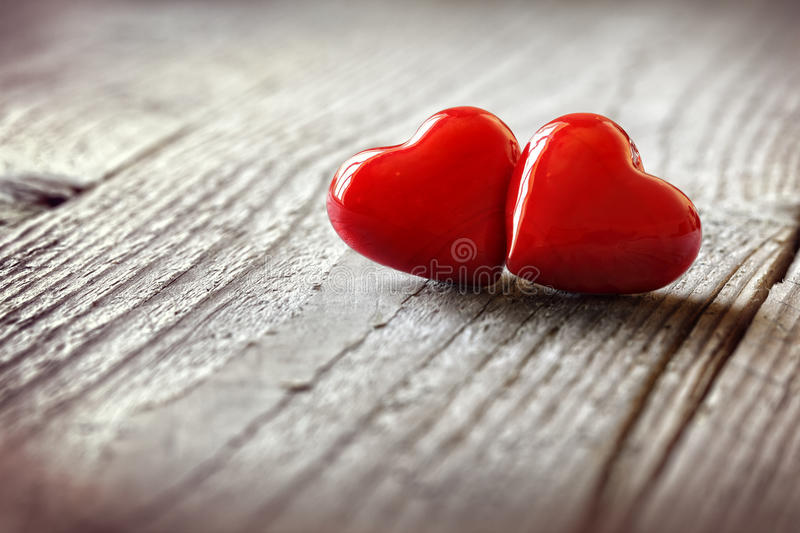 Two hearts in love. Two hearts on a wooden background concept for love, dating and romance with copyspace royalty free stock photo