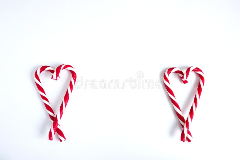 Two hearts made of christmas candy. White and red candy canes in the shape of two hearts on a white background. Copy space royalty free stock image