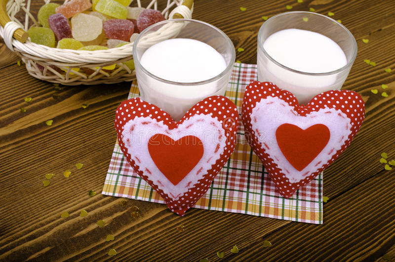 Two hearts, marmalade in a wicker basket and two glasses of milk royalty free stock image