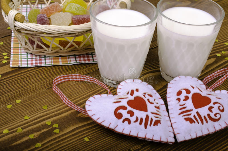 Two hearts, marmalade in a wicker basket and two glasses of milk stock photography