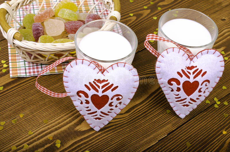 Two hearts, marmalade in a wicker basket and two glasses of milk royalty free stock photo