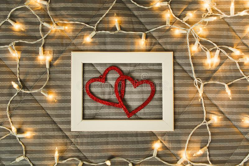 Two hearts in photo frame over plaid with lights, comfort and romance concept with history royalty free stock photography