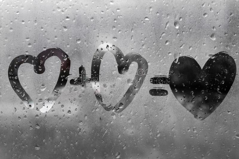 Two hearts with plus sing and equality sign on window in Rainy weather , valentine`s day. Day valentine stock photography