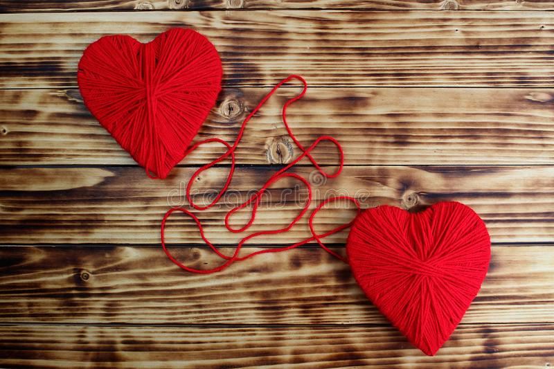 Two hearts of red color tied by a thread lie on a wooden background stock photography