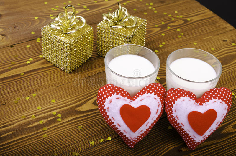 Two hearts and two golden gift and two glasses of milk. stock photo