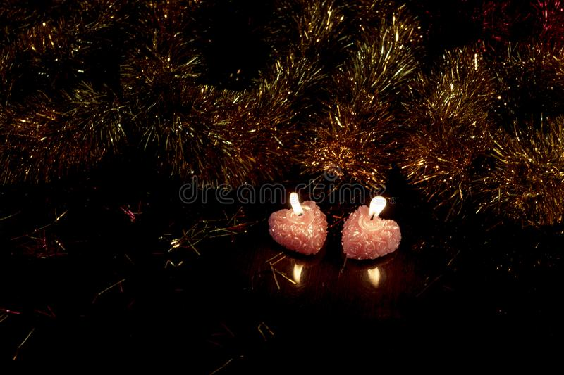 Two hearts, two lights, two candles with a reflection in a dark surface. stock images