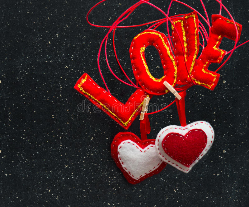 Two hearts and the word love made of fabric. Two hearts and the word love made of fabric on a black background. Symbol of love stock images