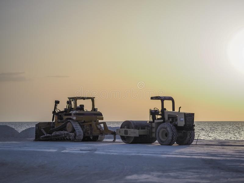 Two heavy equipment vehicles at a construction site on the coast royalty free stock photo