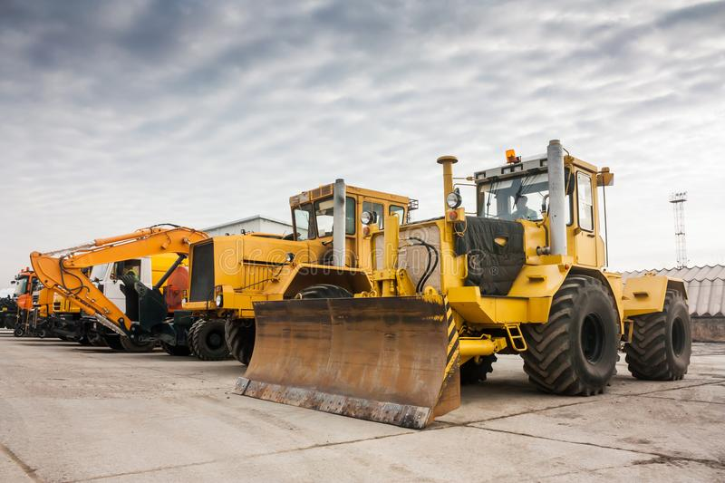 Two heavy wheeled tractor one excavator and other construction machinery. At the outdoor royalty free stock image