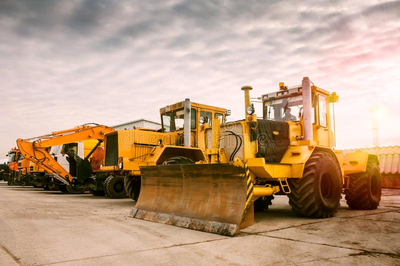 Two heavy wheeled tractor one excavator and other. Construction machinery in the morning sun royalty free stock photo