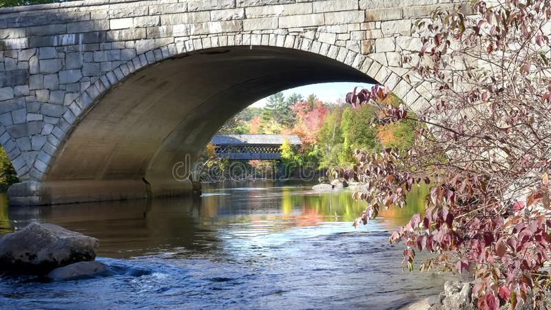 Two henniker bridges in new hampshire with trees in fall colors royalty free stock image