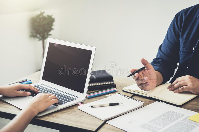Two high school students campus or classmates with helps friend. Studying for a test an exam in workbook learning in classroom, Tutor books with friends royalty free stock images