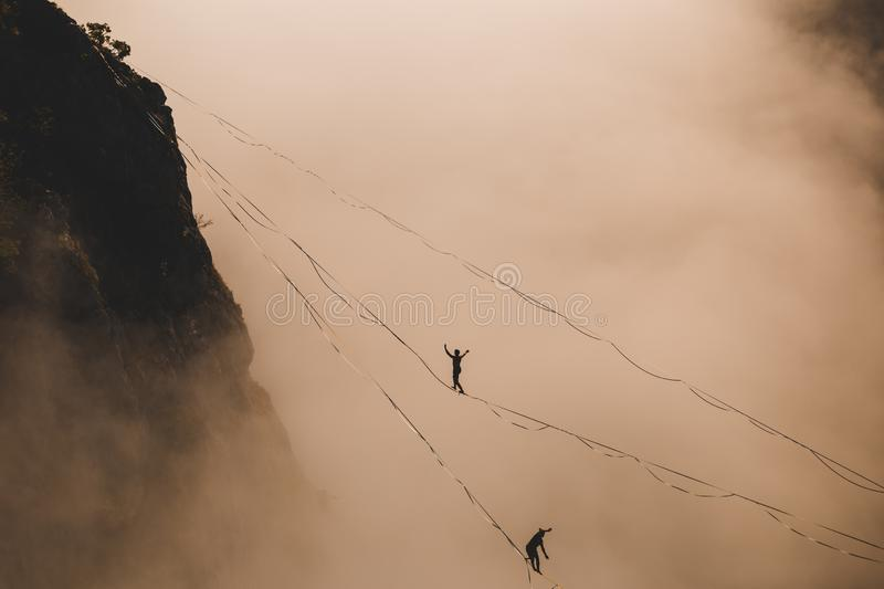 Two highliners are on a line above the cloud. Highliner in the mountains above the canyon. Tightrope walkers over the abyss. A men is walking along a stretched royalty free stock images