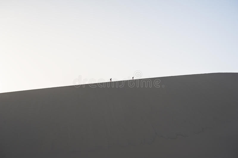 Two Hikers Climb On The Sand Dunes Stock Photos