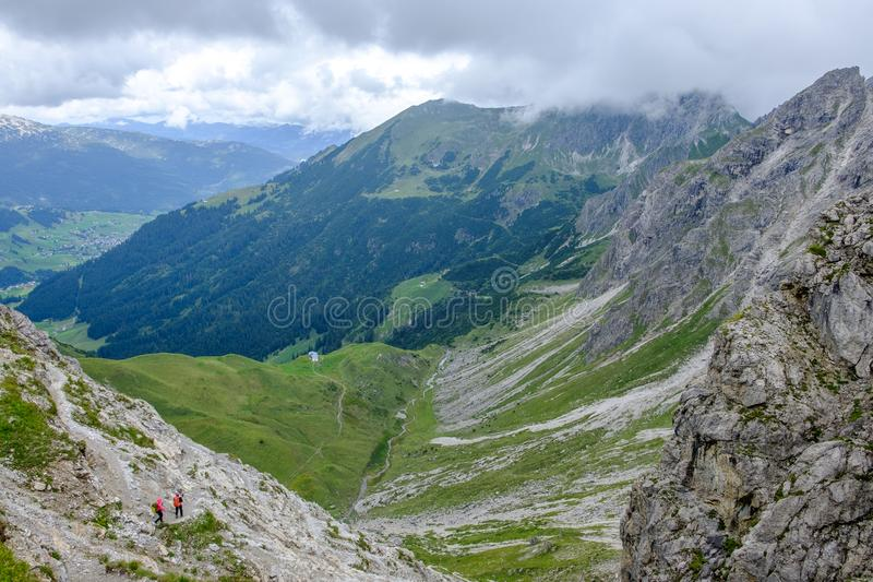 Two hikers descending into a valley in the Allgaeu moutains on a cloudy day, Austria stock photos
