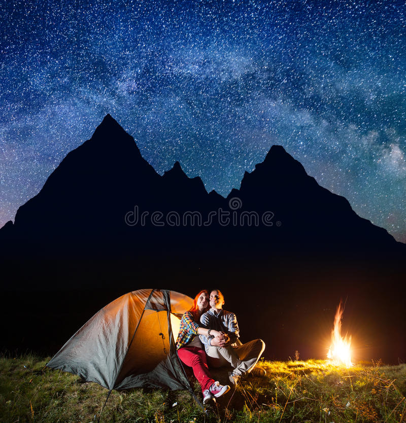 Two hikers having a rest in his camp at night near campfire under shines starry sky. On the background silhouette of the mountains. Astrophotography royalty free stock image