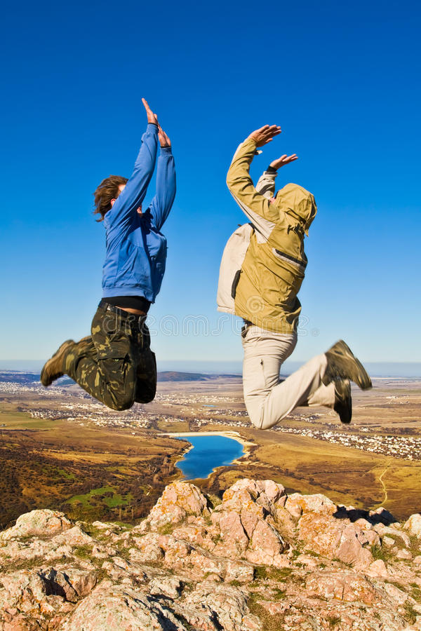 Two hikers jumping cheerfully on mountain summit. In clear sunny weather stock photos